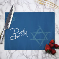 Personalized cutting board with blue background, a lighter blue Star of David and your name or custom text.