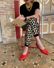 Red ballet flat shoes in larger sizes. Girl in red shoes and leopard print pants.