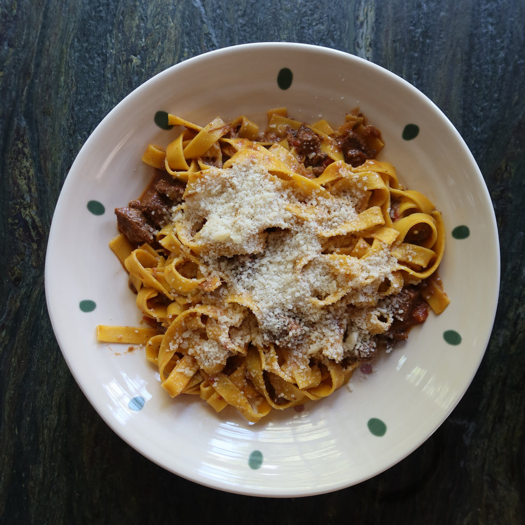 tagliatelle pasta with a meat ragu finished with parmeaan, on a spotted white plate, by Bocca di Lupo