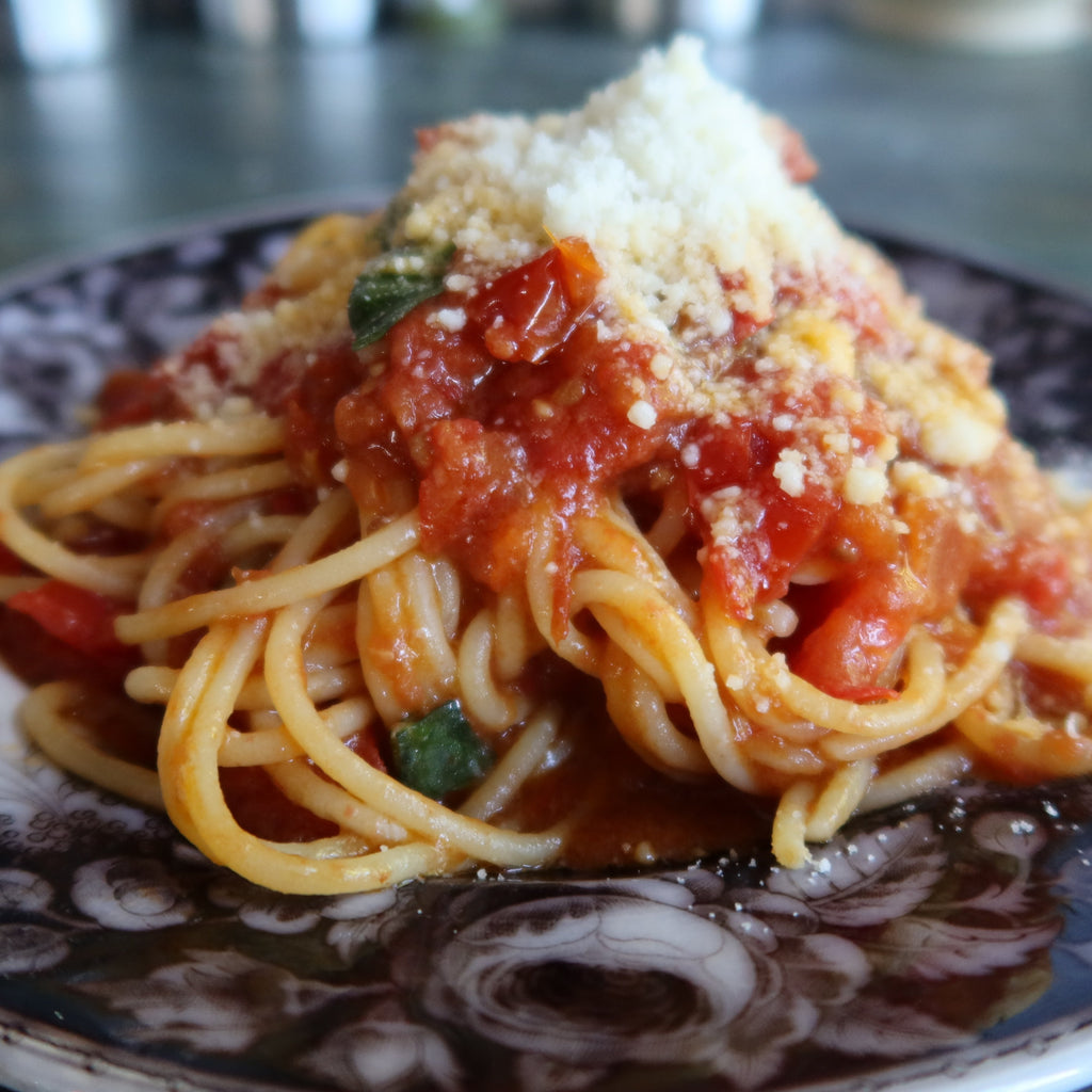 spaghetti with tomato sauce and basil sprinkled with Pecorino cheese, on a black and white plate, by Bocca di Lupo