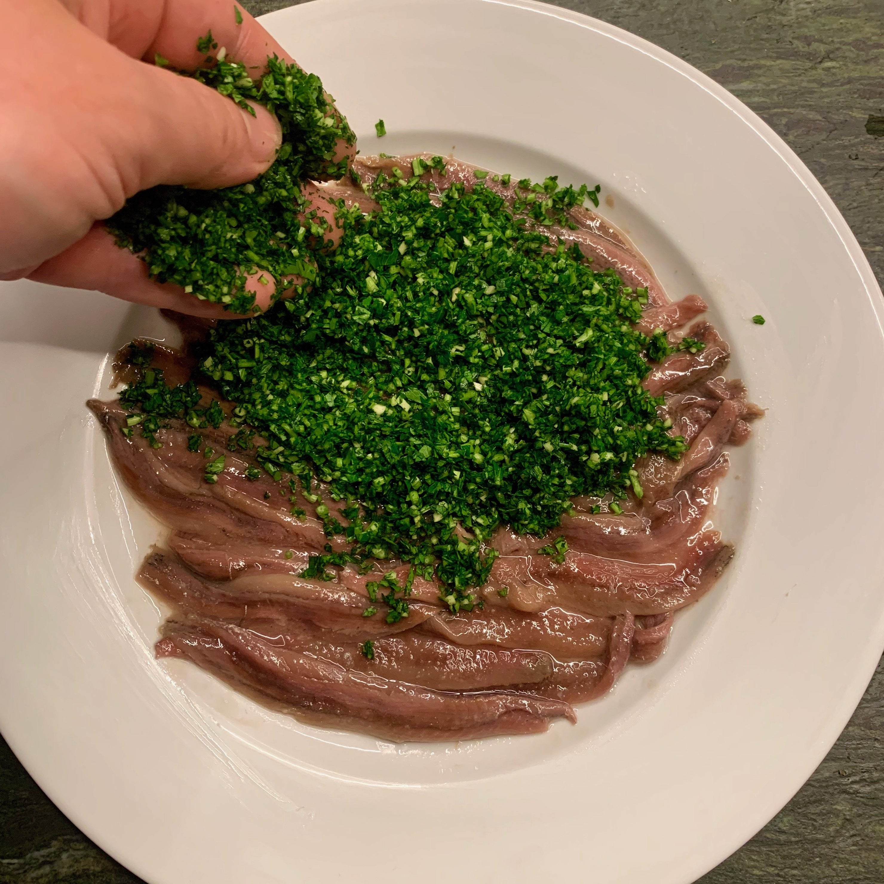Cantabrian anchovies spread over a white plate with parsley and purple garlic being spread over them