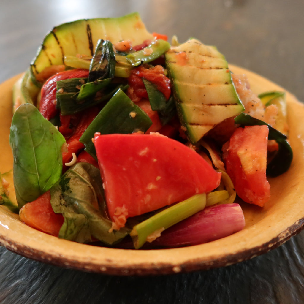 tomato and bread salad with grilled courgettes and Tropea onions in a yellow bowl, by Bocca di Lupo