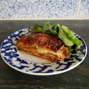 a portion of parmigiana di melanzane garnished with a green salad on a blue and white plate, by Bocca di Lupo
