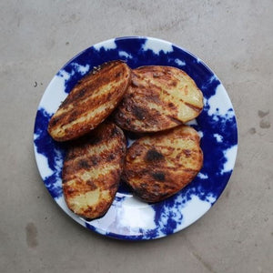 grilled sliced potatoes on a  blue and white plate, by Bocca di Lupo