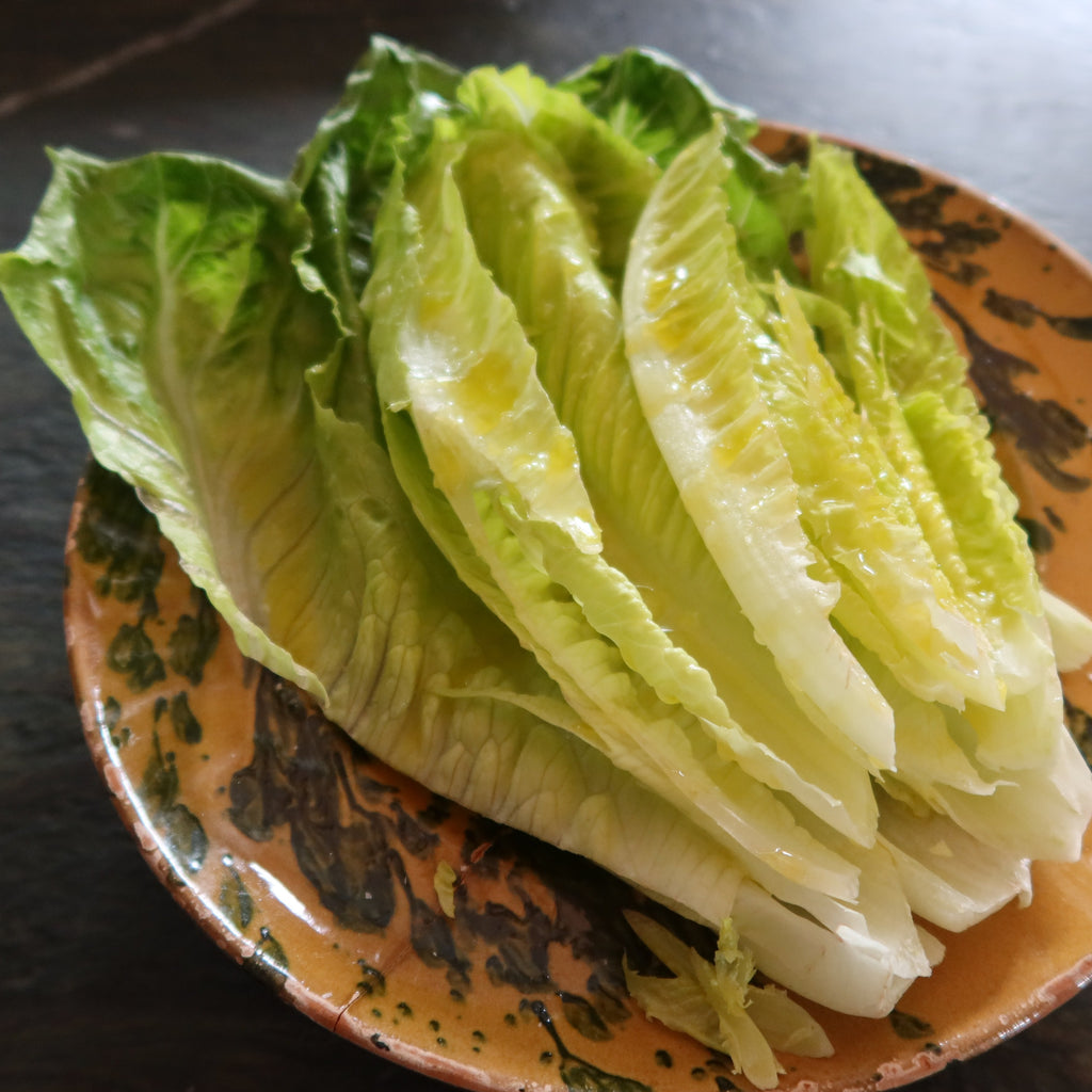 Romaine lettuce dressed with lemon oil on a speckled yellow plate, by Bocca di Lupo