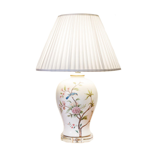 Round shapely ceramic table lamp with an off-white background