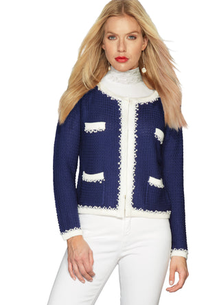 French style little knitted jacket as inspired by Coco Chanel in Royal Blue and paired with white jeans and a white ruffle fine-knit polo neck jumper