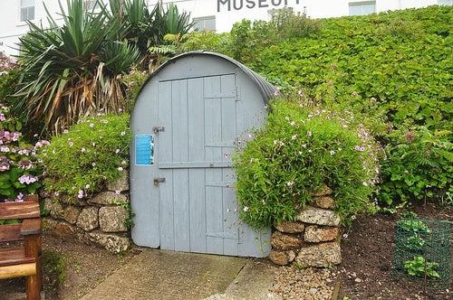 The image shows an Anderson shelter built at PK Porthcurno Museum of Global Communications. The shelter is painted grey with a corrugated metal roof, it is surrounded by a range of greenery.