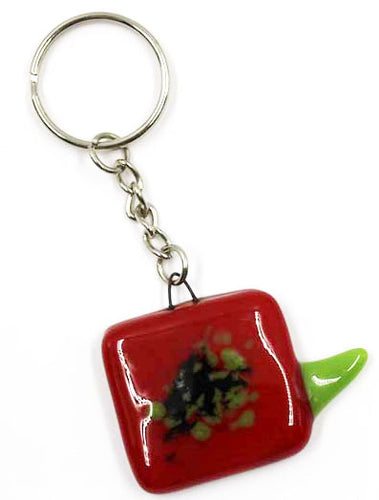 The image shows a square fused-glass poppy head of red glass with black and green centre and a green fused leaf element protruding off it. The poppy is attached to a silver-coloured metal keyring attachment.