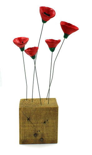 The image shows a cube of wood with five green metal stems coming out of the top of it. At the top of each of the stems is one poppy head made from clay and painted red with a green bottom and black centre.