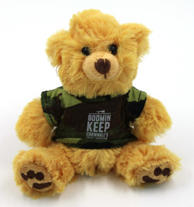 The image shows a 10 centimetre  seated golden brown teddy bear, with brown stiched paw patterns on the feet. The teddy bear is wearing a camouflage t-shirt with the Bodmin Keep: Cornwall's Army Museum logo on the t-shirt in white