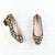 Overhead view of pair of leopard print heeled shoes with scallop edge