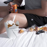 Man wearing lounge shorts in bed eating Chinese food.