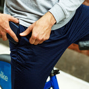 Man putting phone into lounge pant pocket on a bike.