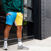 Man wearing fun short lounge shorts outside in front of a garage door.