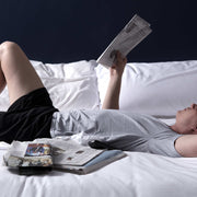 Man reading newspaper in bed wearing pocket lounge shorts.