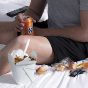 Man eating chinese food on his bed in pocket lounge shorts.