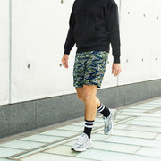 Man wearing tiger stripe lounge shorts and tech varsity socks in black outside with concrete building background.