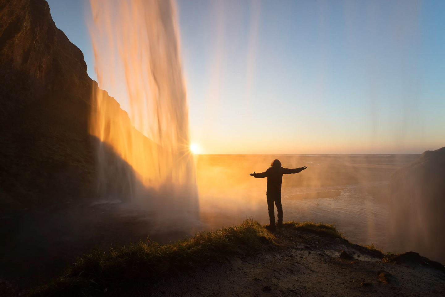 A man standing behind a waterfall as the sun sets on the Iceland beach.