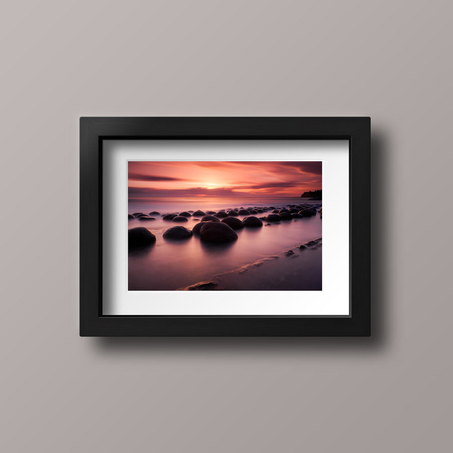 A photography print with a black frame of a vibrant sunset over rocks on a beach in northern California.