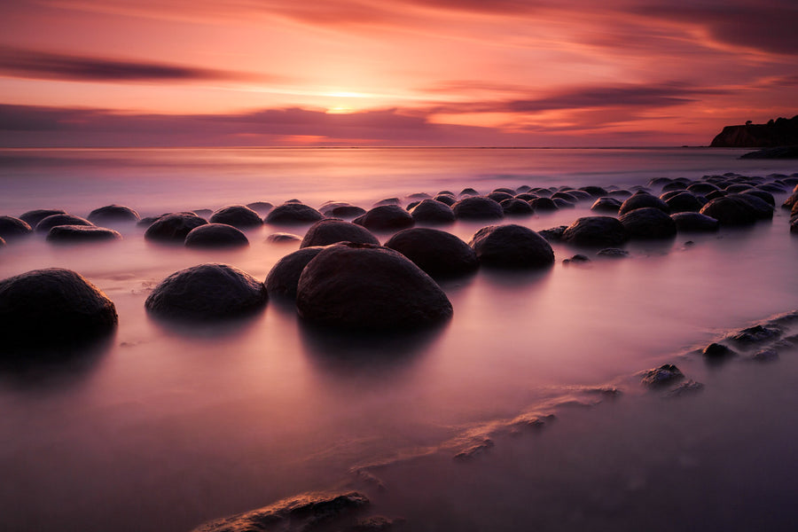 A vibrant sunset over rocks on a beach in northern California.