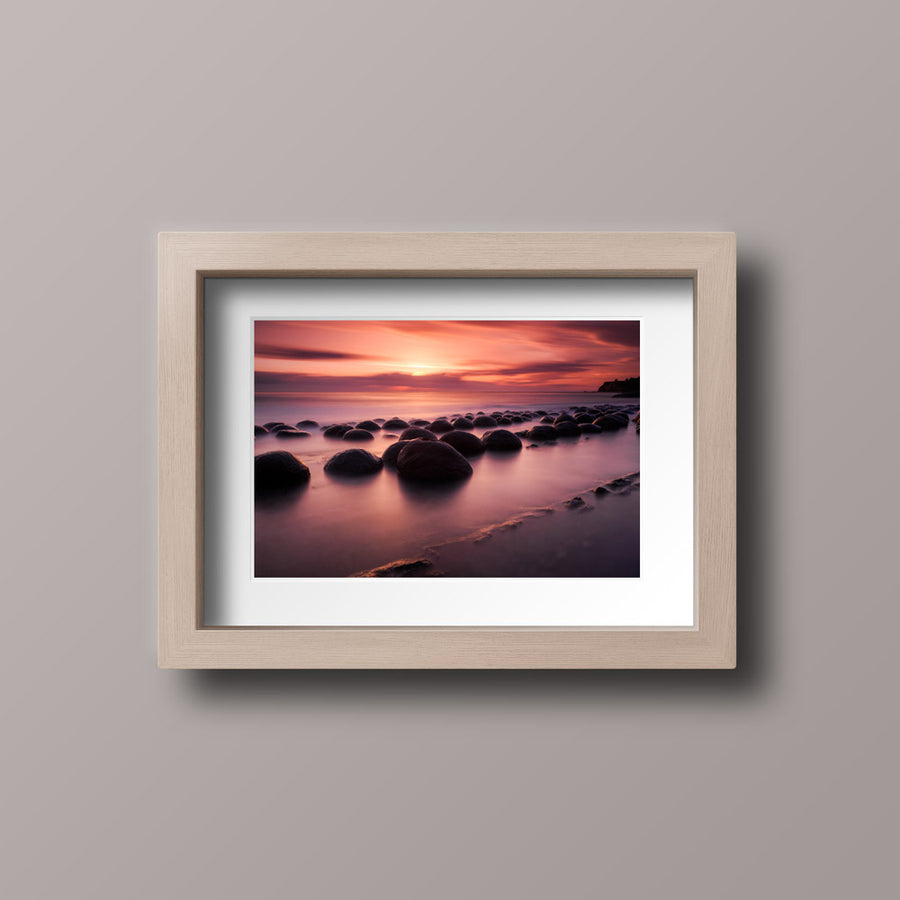 A photography print with a wooden frame of a vibrant sunset over rocks on a beach in northern California.