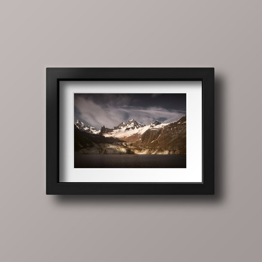 A photographic print with a black frame of the sun rising over John Hopkins Glacier in Glacier Bay National Park.