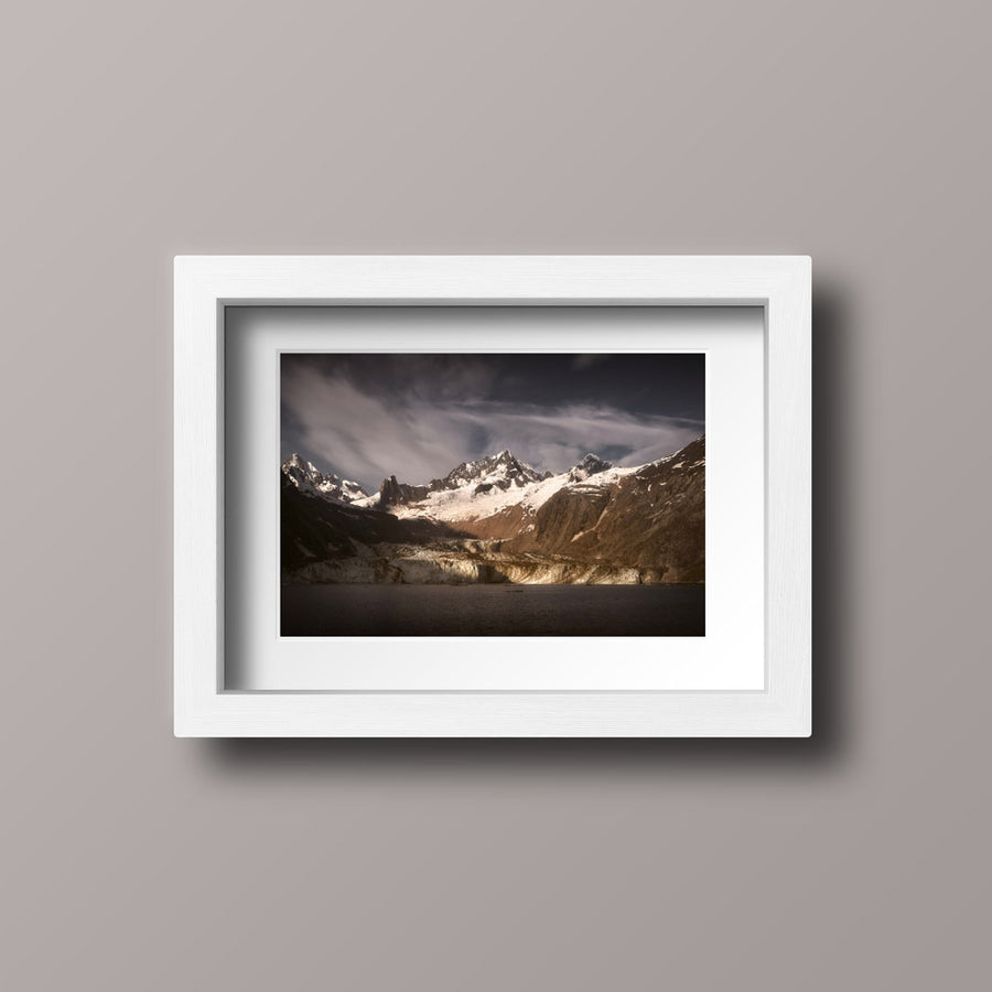 A photographic print with a white frame of the sun rising over John Hopkins Glacier in Glacier Bay National Park.