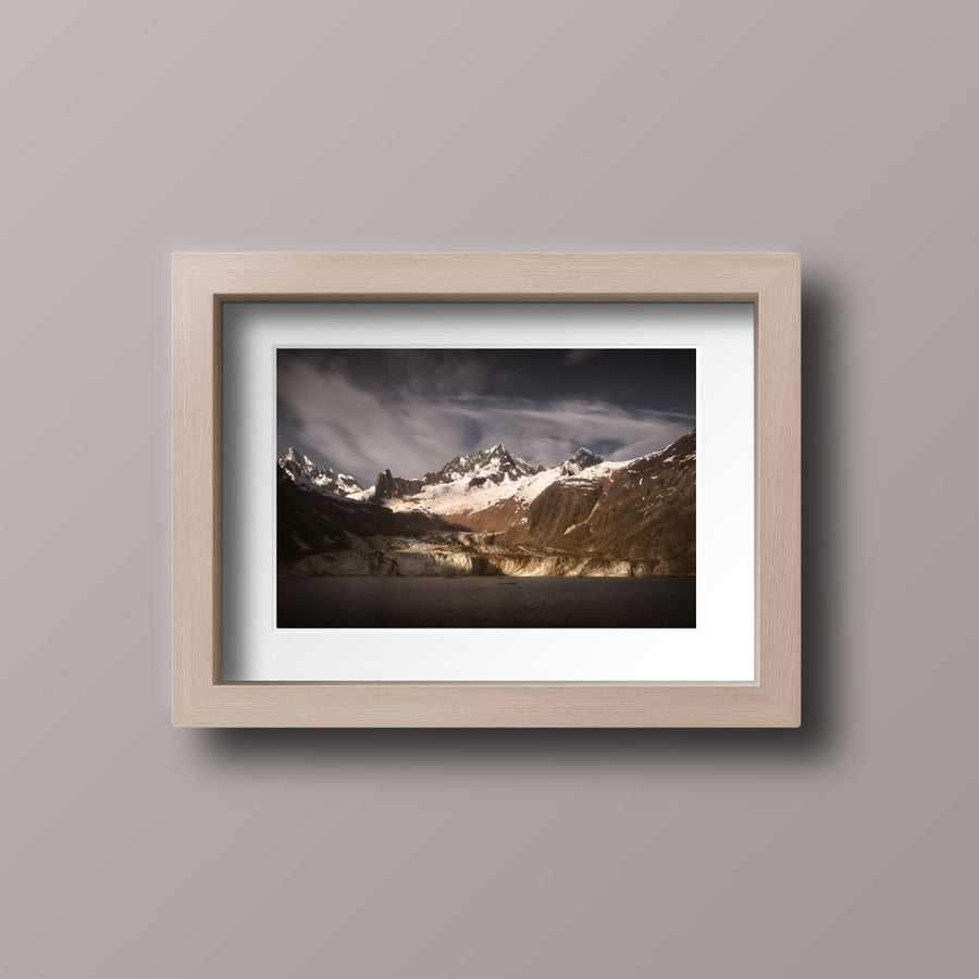 A photographic print with a wooden frame of the sun rising over John Hopkins Glacier in Glacier Bay National Park.