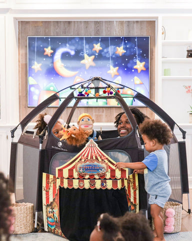 A family playing inside the Pop N Go Playpen for a magic show night