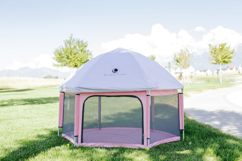 The Pink Pop N Go Playpen assembled outside