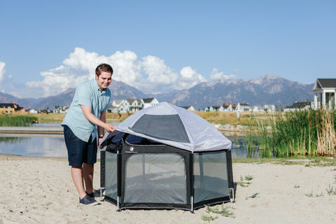 A dad covering the pop n play yard with the UV shade covering to protect from the sun while playing on the lake