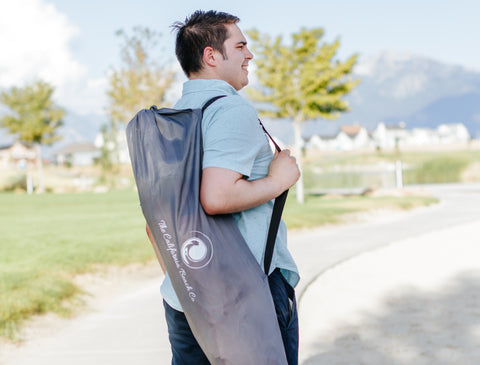 A father carrying the Pop N Go portable playpen within the shoulder strap bag on the way to the beach