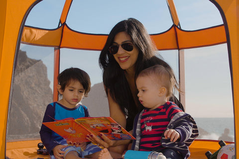 Mother playing with her two toddlers in the pop n' go portable playpen at the beach