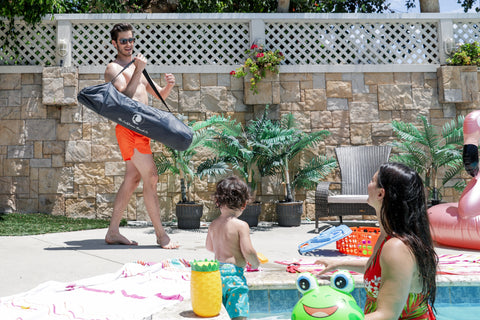 A young family enjoying their day in the pool, dad is bringing out the pop n go playpen for their son to play in