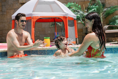 Family playing inside the pool with the Pop N Go Playtent set up as a shady spot
