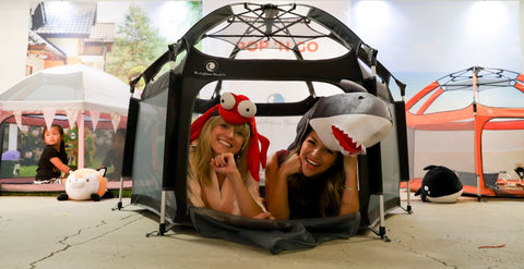 Two young moms laying in the Pop N Go Tent enjoying their time together at the Biggest Baby Shower Ever event