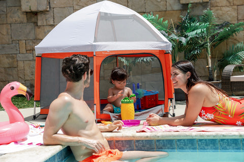 A family using the Pop N Go Playpen while hanging out in the backyard by the pool
