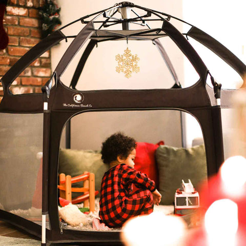 child sitting in playpen on christmas day