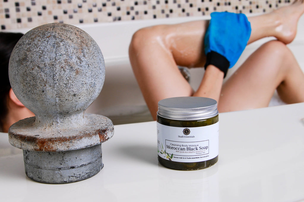Woman experiencing authentic Moroccan hammam spa in her bathtub with organic eucalyptus black soap and kessa mitt.