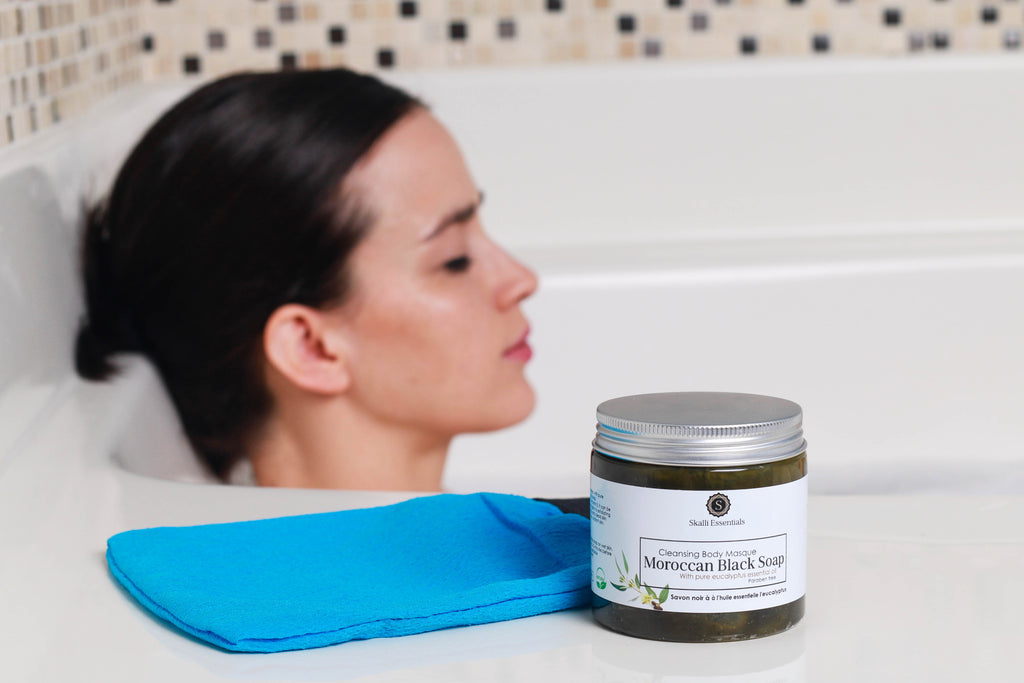 Woman relaxing enjoying Skalli Essentials Moroccan hammam spa black soap with pure eucalyptus essential oil