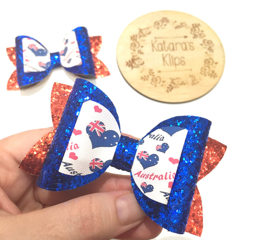 Handmade hair bow in Australia Day theme. Heart shaped Australian Flag and Australia Day text print on blue glitter bow as middle layer. Red glitter bow on bottom layer