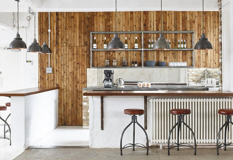 A white industrial bar with hanging lights by Industville