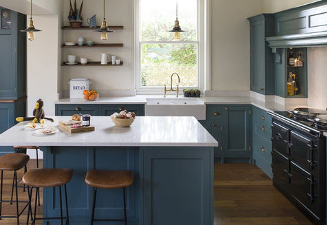 Modern style kitchen decor with teal cabinets and industrial pendants