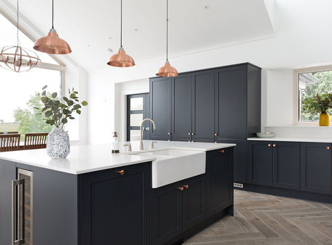 Dark kitchen interior with trio of copper pendants above kitchen island