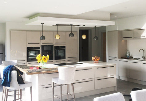 Open plan neutral kitchen interior with industrial lighting above kitchen island