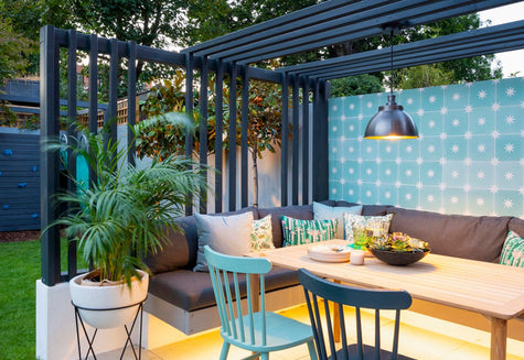 An outdoor dining area with plants and industrial lights by Industville