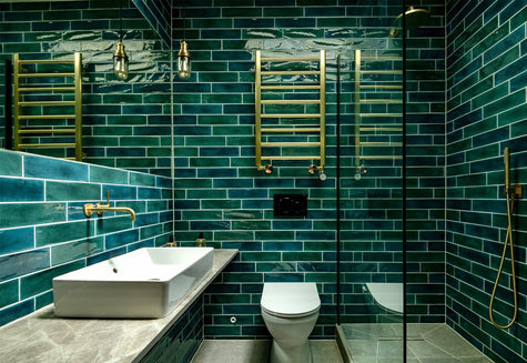 A contemporary bathroom with green tiling and brass furnishings