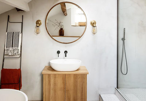 Nude bathroom interior with brass lights and oval mirror