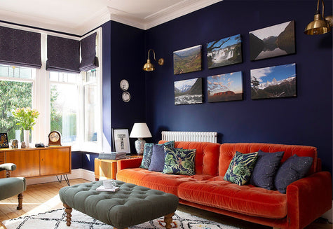 A contemporary living room with dark blue wall and brass lighting
